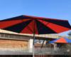 Runder Großschirm mit blauen und roten Tuchsegmenten auf einer Dachterrasse einer Kita.